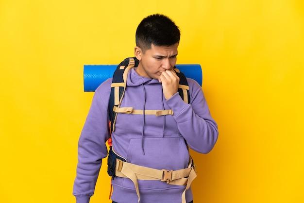 Junger bergsteigermann mit einem großen rucksack lokalisiert auf gelbem hintergrund, der zweifel hat