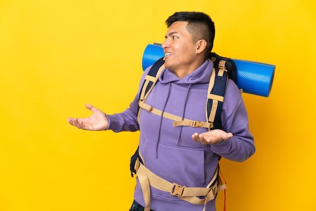 Junger bergsteigermann mit einem großen rucksack lokalisiert auf gelbem hintergrund mit überraschungsausdruck beim betrachten der seite
