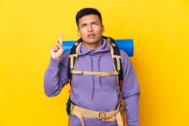 Junger bergsteigermann mit einem großen rucksack lokalisiert auf gelber wand, der eine idee denkt, die den finger nach oben zeigt