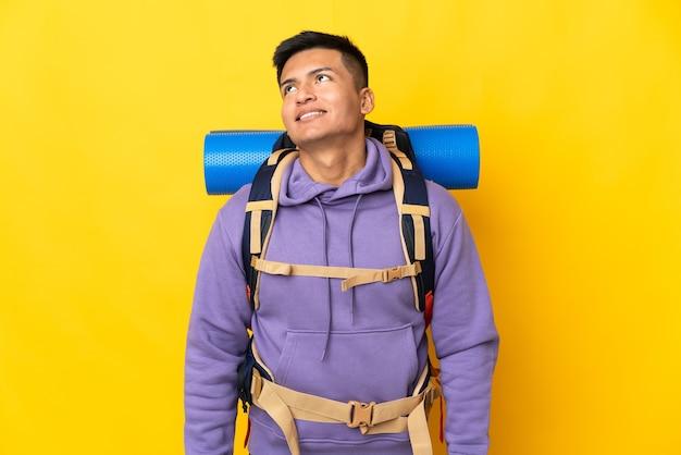 Junger bergsteigermann mit einem großen rucksack lokalisiert auf gelber wand, die eine idee beim aufschauen denkt