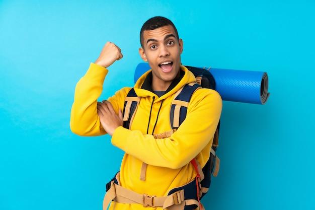 Junger bergsteigermann mit einem großen rucksack über der lokalisierten blauen wand, die starke geste macht