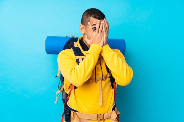 Junger bergsteigermann mit einem großen rucksack über isolierten blauen wandverkleidungsaugen und blick durch finger