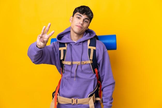 Junger bergsteigermann mit einem großen rucksack über isolierter gelber wand glücklich und drei mit den fingern zählend