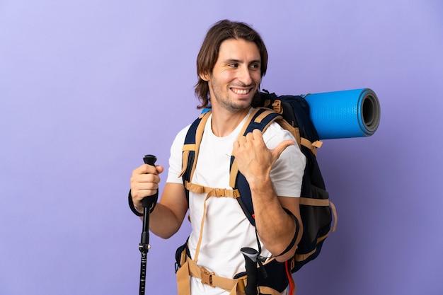 Junger bergsteigermann mit einem großen rucksack über isolierter wand, die zur seite zeigt, um ein produkt zu präsentieren