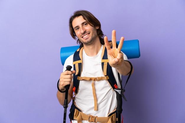 Junger bergsteigermann mit einem großen rucksack über lokalisiertem hintergrund glücklich und zählt drei mit den fingern