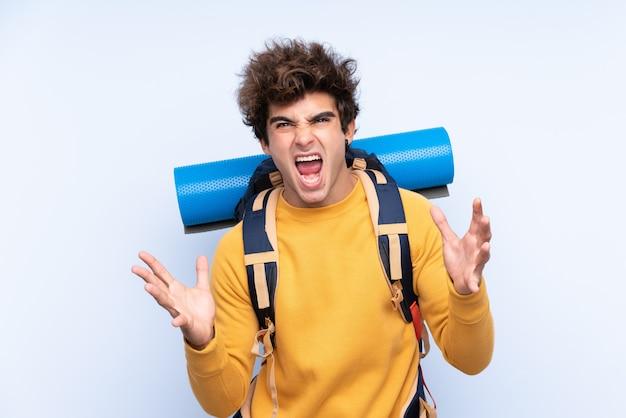Junger bergsteigermann mit einem großen rucksack über lokalisierter blauer wand unglücklich und mit etwas frustriert