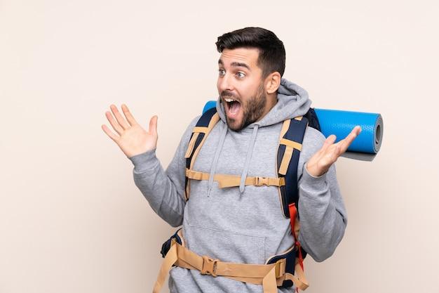 Junger bergsteigermann mit einem großen rucksack über lokalisierter wand mit überraschungsgesichtsausdruck