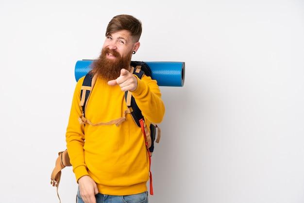 Junger bergsteigermann mit einem großen rucksack über weißer wand zeigt finger auf sie