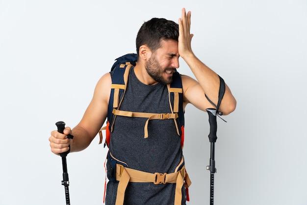Junger bergsteigermann mit einem großen rucksack und wanderstöcken auf weißer wand, die zweifel mit verwirrendem gesichtsausdruck haben