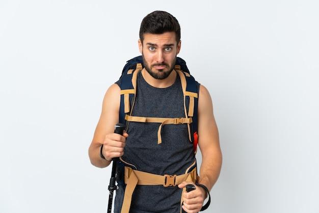 Junger bergsteigermann mit einem großen rucksack und wanderstöcken lokalisiert auf weiß traurig