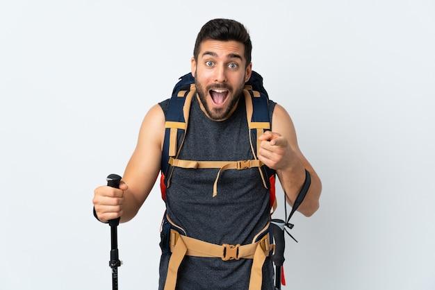Junger bergsteigermann mit einem großen rucksack und wanderstöcken lokalisiert auf weißer wand zeigt finger auf sie