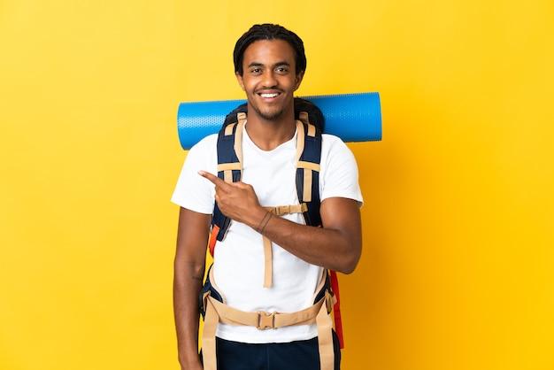 Junger bergsteigermann mit zöpfen mit einem großen rucksack lokalisiert auf gelbem hintergrund, der zur seite zeigt, um ein produkt zu präsentieren