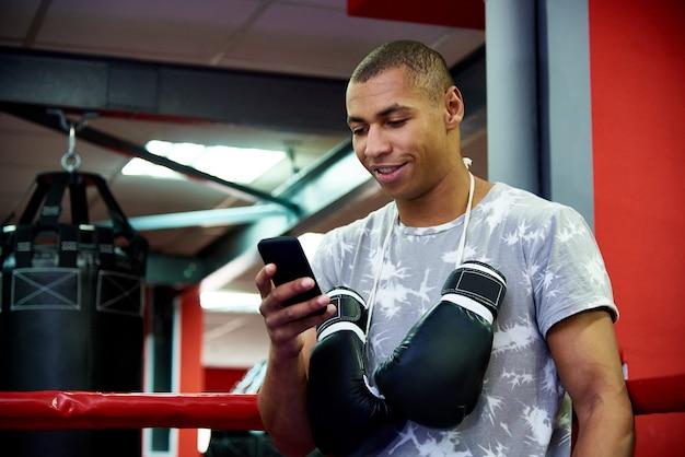 Junger berufsboxer mit einem telefon im ring auf hintergrund der turnhalle mit taschen.