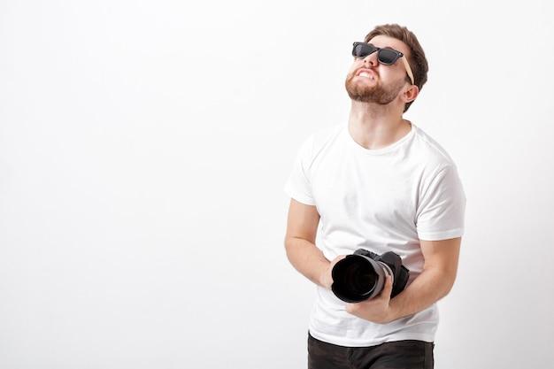 Junger berufsfotograf in einem weißen hemd hält eine schwere digitalkamera mit einem langen objektiv. harte arbeit