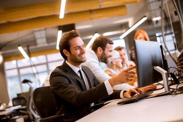 Junger berufsgeschäftsmann benutzt einen laptop für arbeit im büro