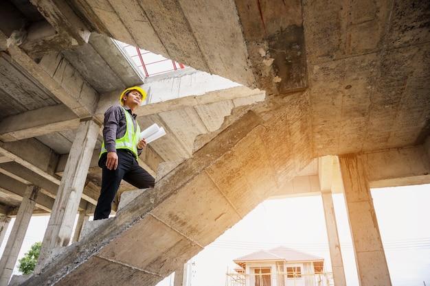 Junger berufsingenieur mit schutzhelm und blaupausenpapier auf der baustelle des hausbaus