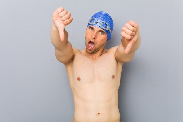 Junger berufsschwimmermann, der unten daumen zeigt und abneigung ausdrückt.