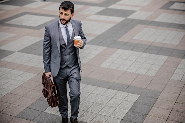 Junger beschäftigter mann im anzug, der tasse mit kaffee in einer hand, aktentasche in der anderen hält und zur arbeit geht.