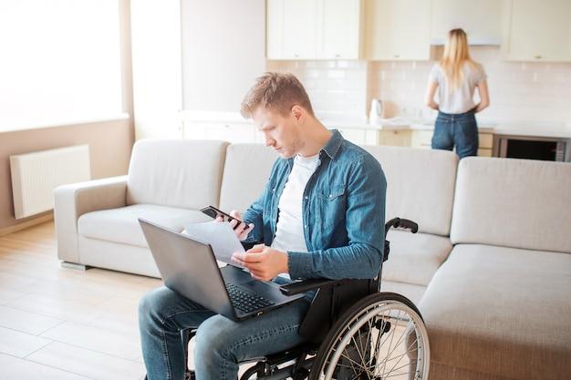 Junger beschäftigter mann mit behinderung, die auf rollstuhl sitzt. halten sie den laptop auf die knie. junge frau stehen hinter und kochen. tageslicht im raum.