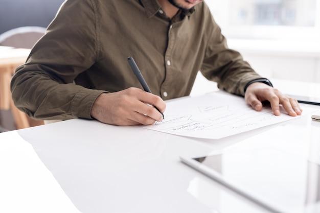 Junger beschäftigter ökonom, der flussdiagramm auf papier zeichnet, während er durch schreibtisch im büro sitzt und bericht vorbereitet