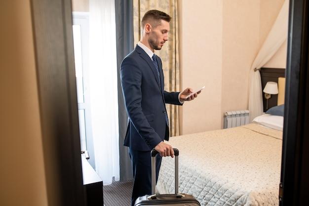 Junger beschäftigter unternehmer in der abendgarderobe, der smartphone verwendet, um taxi zu rufen, während er hotel zum flughafen verlässt