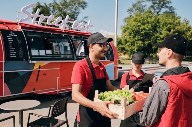 Junger besitzer eines streetfood-trucks, der eine kiste mit frischem gemüse nimmt