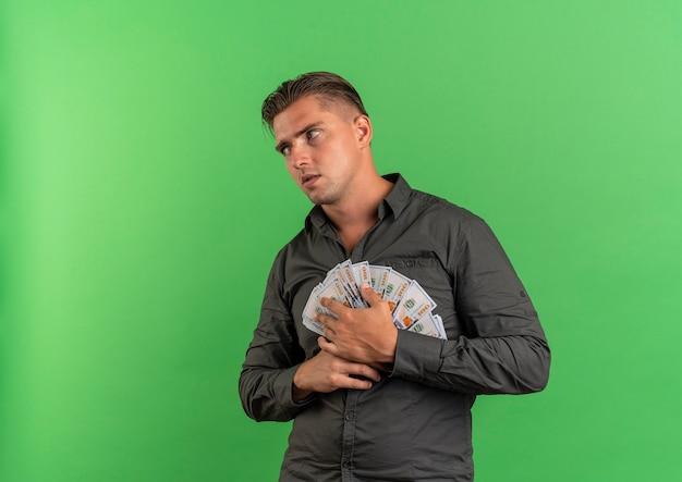 Junger besorgter blonder gutaussehender mann hält geld, das die seite lokalisiert auf grünfläche mit kopienraum betrachtet