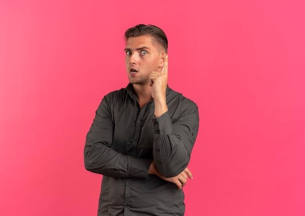 Junger besorgter blonder gutaussehender mann zeigt lokalisiert auf rosa hintergrund mit kopienraum