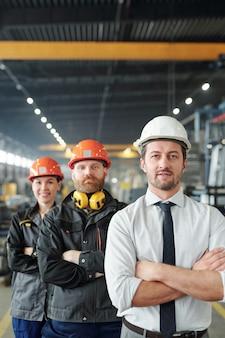 Junger, bewaffneter leiter des ingenieurteams und seine erfolgreichen auszubildenden im posieren von arbeitskleidung