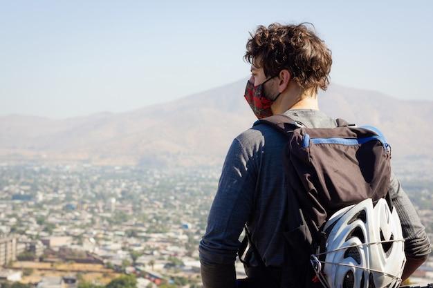Junger biker mit gesichtsbedeckung und helm auf rucksack mit blick auf die stadt an einem sonnigen tag von oben