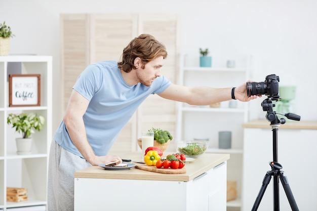 Junger blogger, der die kamera einstellt und sich auf online-kommunikation vorbereitet. er wird gesundes essen kochen