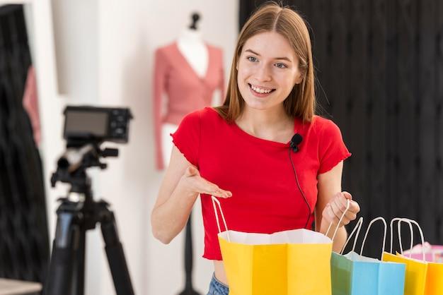 Junger blogger, der lächelt und eine einkaufstasche hält