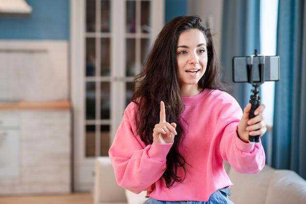 Junger blogger, der selfie-stick benutzt und mit dem telefon spricht