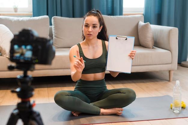 Junger blogger, der trainingsplan vor der kamera präsentiert