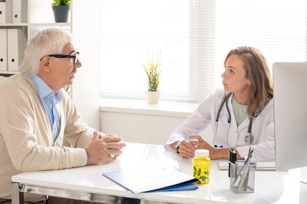 Junger blonder arzt des medizinischen beraters, der am arbeitsplatz sitzt, mit dem älteren patienten spricht und ihm einige empfehlungen gibt