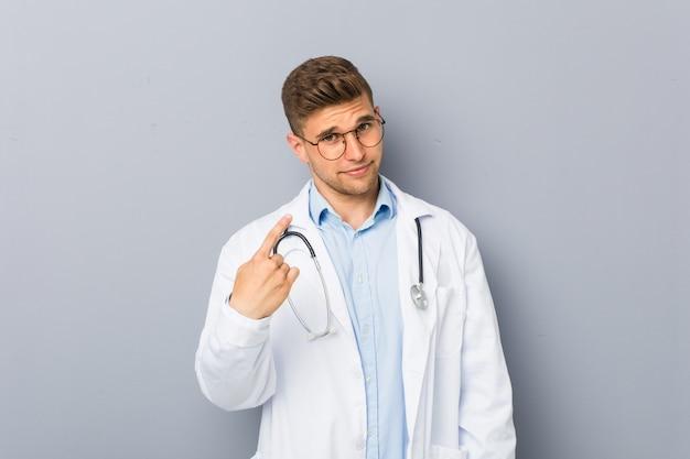 Junger blonder doktormann, der mit dem finger auf sie zeigt, als ob einladung näher kommen.