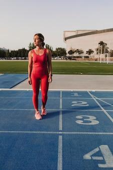 Junger blonder eignungsfrauenläufer an der blauen bahn des stadions bei sonnenuntergang. sport und gesundes lebensstilkonzept