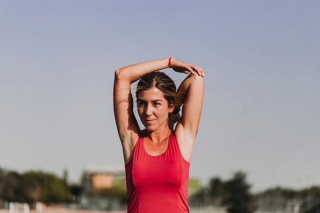 Junger blonder eignungsfrauenläufer, der arme auf blauer bahn des stadions bei sonnenuntergang ausdehnt.