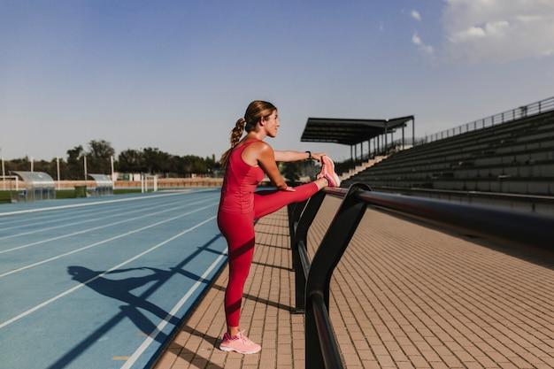 Junger blonder eignungsfrauenläufer, der beine auf blauer bahn des stadions bei sonnenuntergang ausdehnt. sport und gesundes lebensstilkonzept