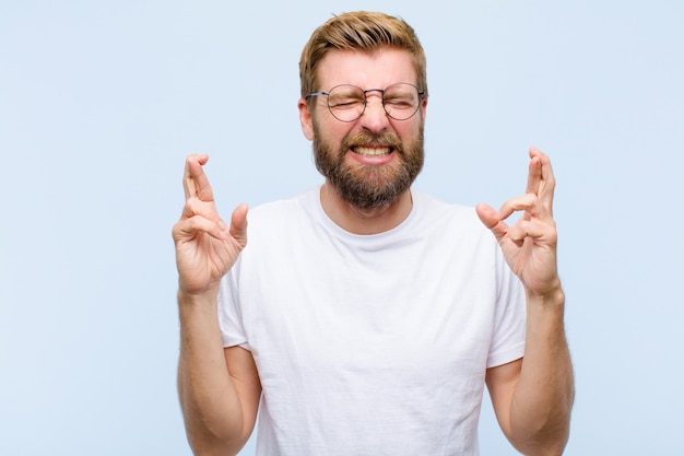 Junger blonder erwachsener mann, der beide finger besorgt und wünschend lächelt und besorgt kreuzt oder auf gutes glück hofft