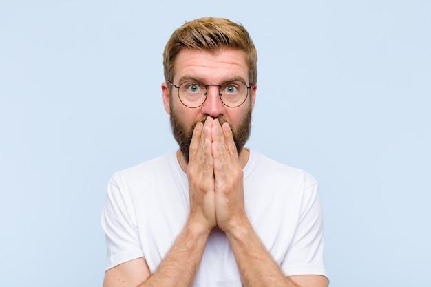 Junger blonder erwachsener mann, der besorgtem umkippen und erschrockenem bedeckungsmund mit den händen schauen besorgt und oben verwirrt glaubt