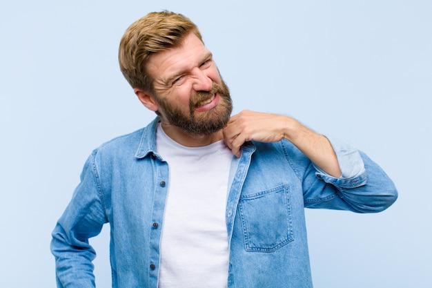 Junger blonder erwachsener mann, der betont, besorgt, müde und frustriert sich fühlt, den hemdhals ziehend und schauen mit problem frustriert