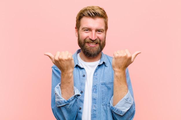 Junger blonder erwachsener mann, der froh lächelt und glücklich schaut, mit beiden daumen oben sorglos und positiv sich fühlt