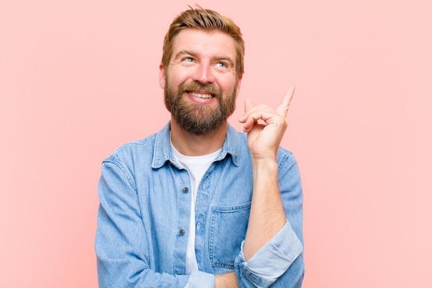 Junger blonder erwachsener mann, der glücklich lächelt und seitlich schaut, sich wundert, eine idee denkt oder hat