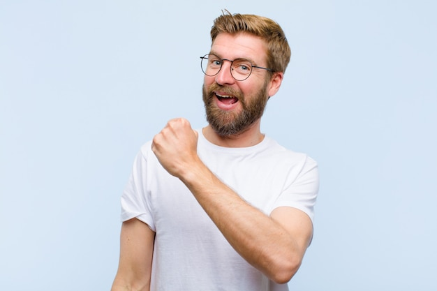 Junger blonder erwachsener mann, der glücklich, positiv und erfolgreich sich fühlt, motiviert, wenn er einer herausforderung gegenübersteht oder gute ergebnisse feiert
