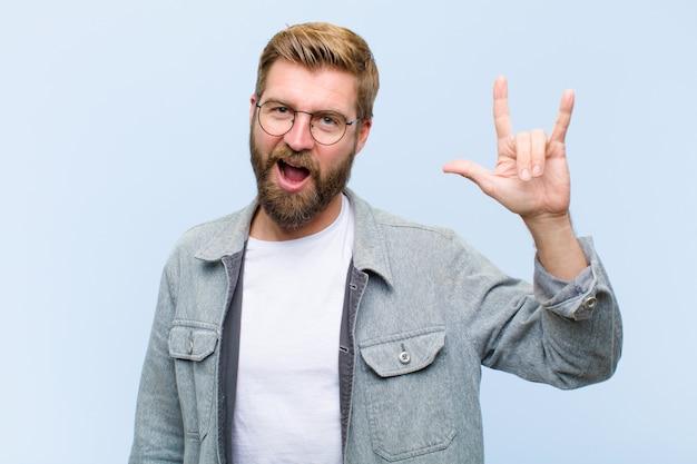 Junger blonder erwachsener mann, der glücklich, spaß, überzeugt, positiv und rebellisch sich fühlt und felsen oder schwermetallzeichen mit der hand macht