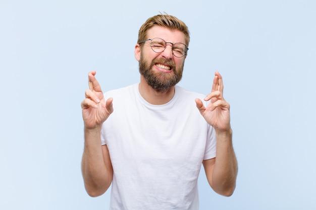 Junger blonder erwachsener mann, der nervös und hoffnungsvoll sich fühlt, finger kreuzt, für gutes glück betet und hofft