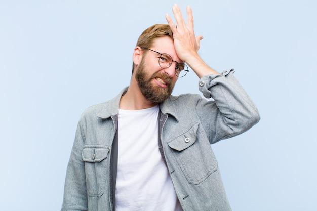 Junger blonder erwachsener mann, der palme zur stirn anhebt, die oops denkt, nachdem er einen dummen fehler gemacht oder sich erinnert hat und sich stumm gefühlt hat