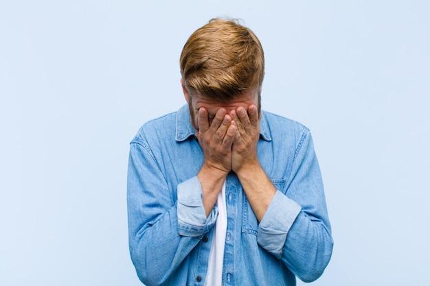 Junger blonder erwachsener mann, der traurig, frustriert, nervös und deprimiert sich fühlt und das gesicht mit beiden händen bedeckt und schreit