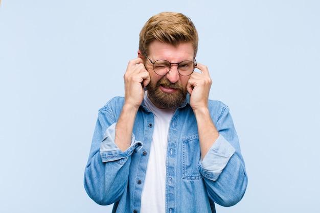 Junger blonder erwachsener mann, der verärgert, betont und gestört schaut und beide ohren zu einem ohrenbetäubenden geräusch, einem ton oder einer lauten musik bedeckt